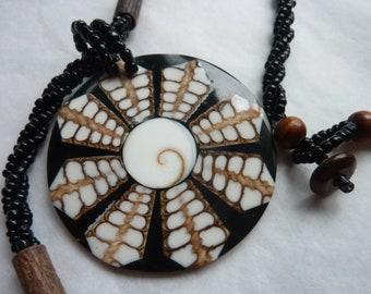 pendant, sea urchin shell, black, handmade glass beads