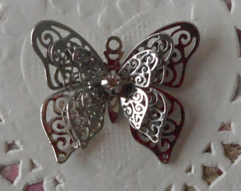 Butterfly charm in silver finely perforated with a glass rhinestones in the center of 3.00 cm wide.