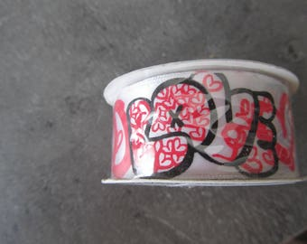 "Satin ribbon marked ""Love"" with hearts in red, black and white tones"