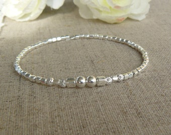 Sterling Silver Stretch Bracelet with smooth, striped and sterling silver square beads