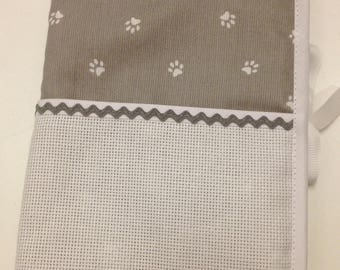 Health book has cross-stitch, dog paws.