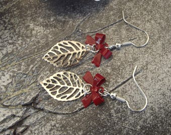 Earrings dangle hooks silver metal with a dot dark red bow charm and a silver stylized leaf.