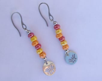 Earrings hooks silver hooks with shiny beads red/orange/yellow/silver color and pattern stylized lotus charm.