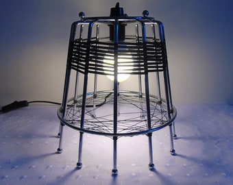 Stainless steel table lamp made from a recycled object