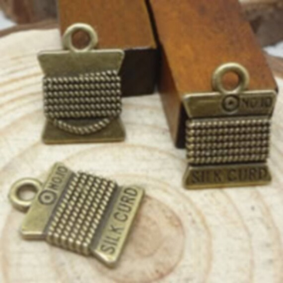 """Set of 5 charms """"Spool of thread"""" bronze size 15 x 11 mm"""