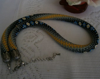 Spiral necklace made with CROCHET with small blue and white flowers