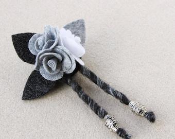 Spilla con rose in panno e feltro grigio-bianco e foglie nere.