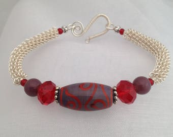 Silver wirework bracelet, with red and purple lampwork focal bead.