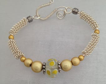 Silver wirework bracelet, with yellow glass lampwork focal bead.