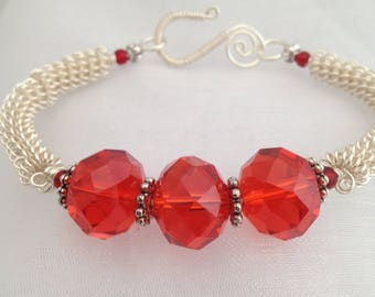 Silver wirework bracelet, with red glass faceted rondelle beads.