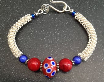 Silver wirework bracelet, with red and blue spotted lampwork focal bead.