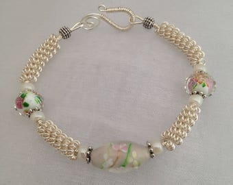 Silver wirework bracelet, with white floral lampwork beads.