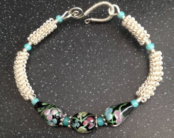 Silver wirework bracelet, with floral glass lampwork beads.