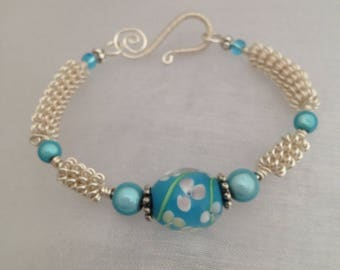 Silver wirework bracelet with blue glass lampwork focal bead.