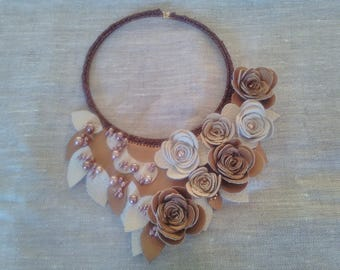 Knitted round necklace with bronze-coloured yarn and various decorations in faux leather.