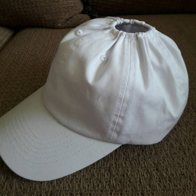 White baseball hat with an elastic hole for ponytail.  33fe8c79930
