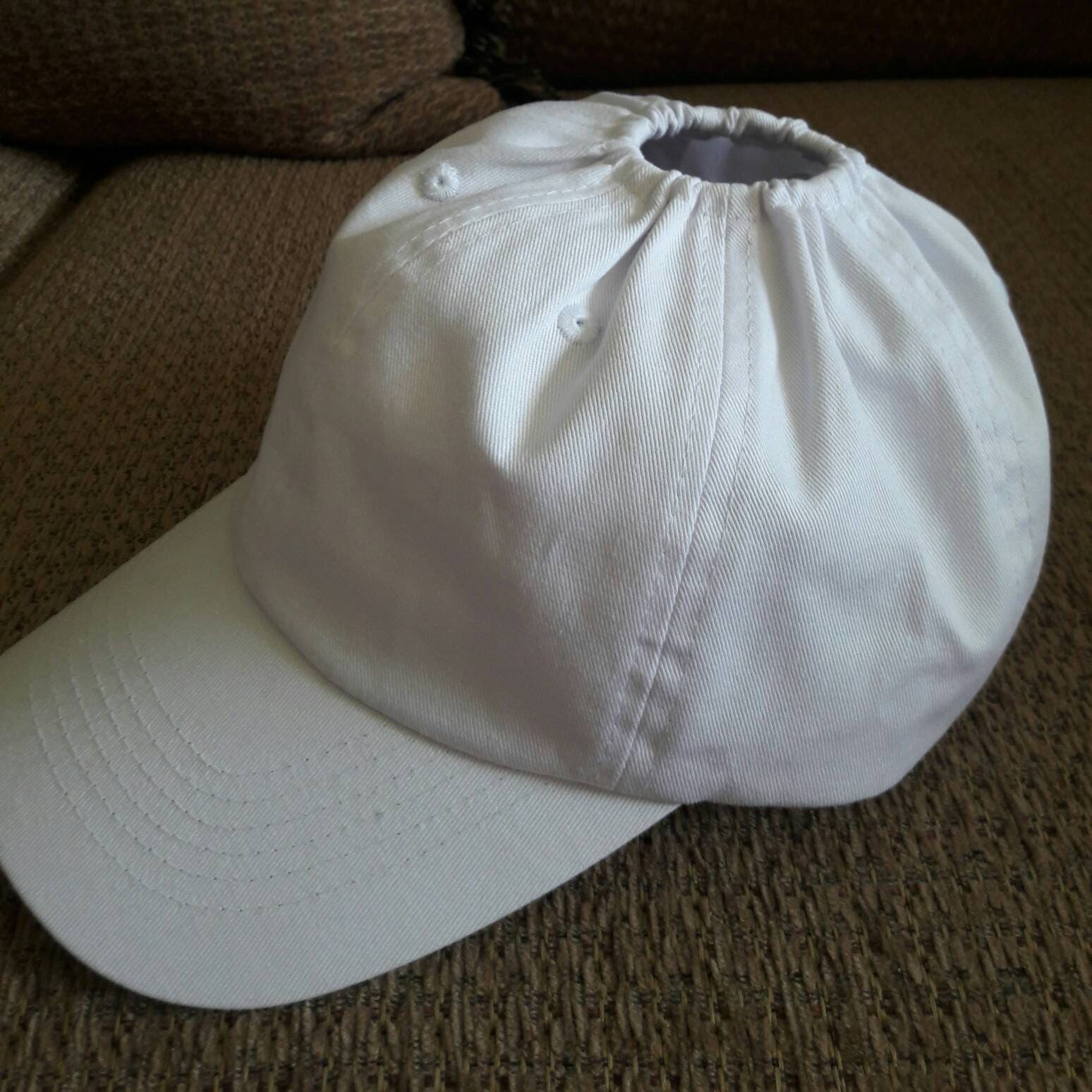 White baseball hat with an elastic hole for ponytail.  8adde6b462c