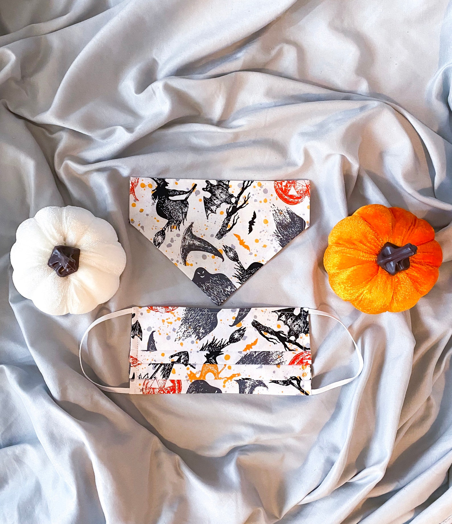 You and your pup can match in this bandana and face mask set with a print of witches, witches hat with orange pumpkins on white fabric. They lay on a light gray fabric between a white and orange pumpkin.