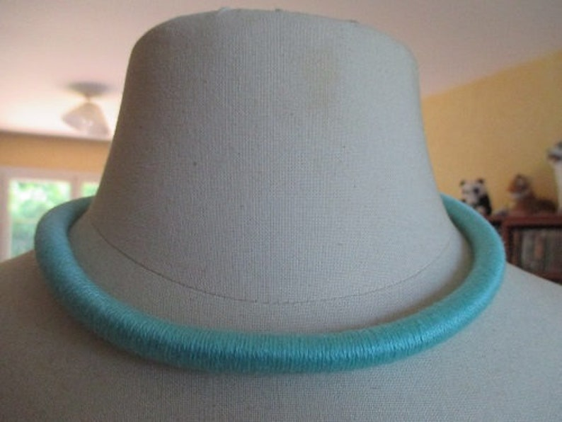 minimalist collar at the metal neck covered with green cotton