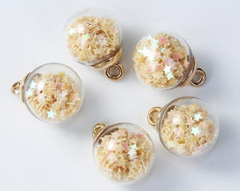 Charm / pendant glass globe filled with beige stars