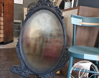 Large oval-shaped mirror. The frame was treated with graphite-colored gypsum paints and copper reflections on the relief decorations.