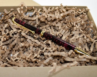 Red and black ebonite twist pen with gold hardware