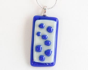 """Fun, blue polka dots on a white background, fused glass; Piece is 1.5"""" long and .9"""" wide. Pendant hangs on a 18"""" silver necklace. #208"""