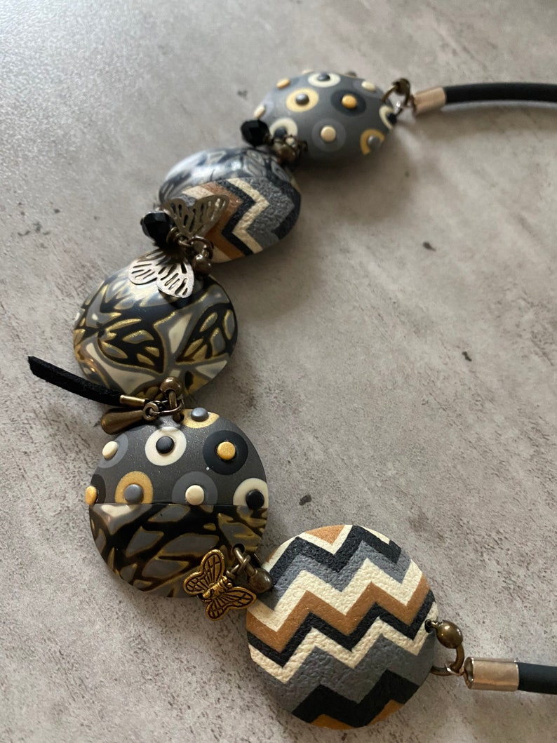 camel and gold polymer clay with metal charms and Swaro pearl. Short necklace in anthracite ecru