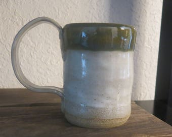 Rustic mug made from Missouri Gold clay.  Copper blue & Eggshell glaze.  Textured handle.  Holds 8 ounces.