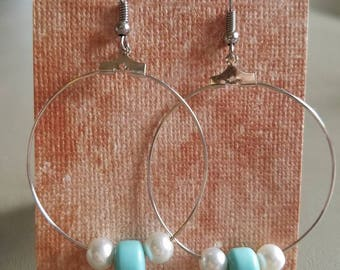 Blue and white beads strung into the hoop earrings
