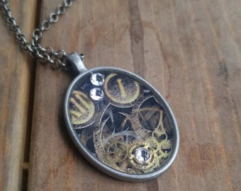 Timeframe - hand crafted resin pendant necklace in matte silver oval base with steampunk imagery and findings, and Swarovski crystals