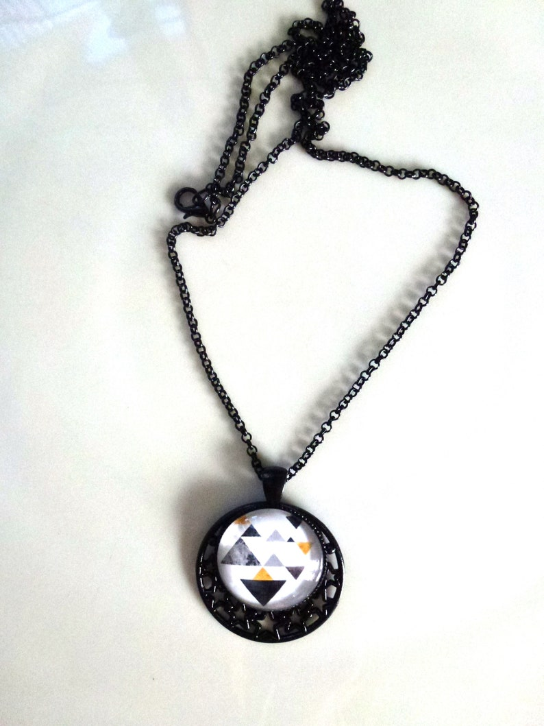 necklace pendant round caochons geometric patterns adornment earrings black metal chain greyblackyellow on white background