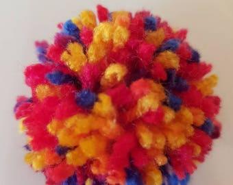 A handmade multi-coloured Pom Pom brooch