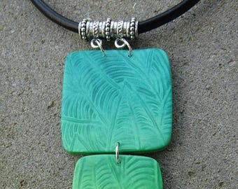 """Pendant """"Under the tropics"""" in polymer clay in shades of green mother of Pearl leaf motifs on leather cord"""