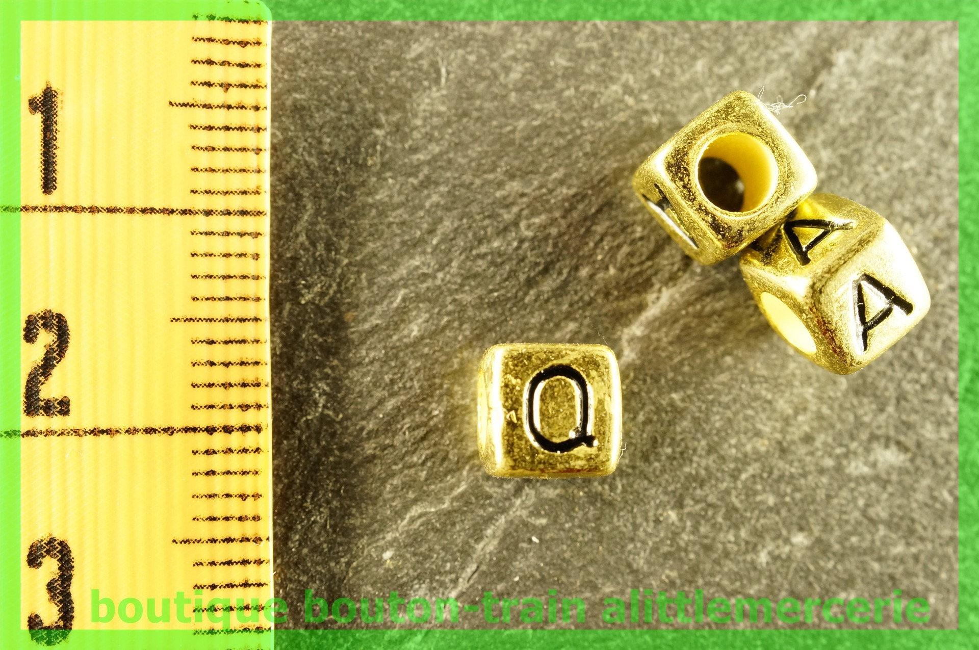 perle perle perle lettre Q plastique cube alphabet doré et noir. dc2920