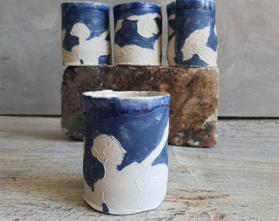 Tasse en céramique bleu et blanc avec dessin. Tasse à café ou tasse pour le thé artisanal, dessin de femme avec un oiseau et des feuilles.
