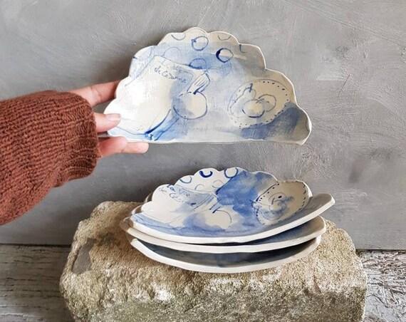 Assiette en forme de nuage avec dessin d'artiste bleu et blanc. Petite assiette en poterie artisanale decoré d'un dessin de livre fruit.