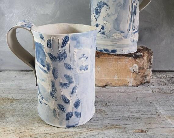 Pichet en poterie artisanale avec poignée . Décoré avec un dessin de femme qui lit et d'un émail crème, cruche en grès artisanale.
