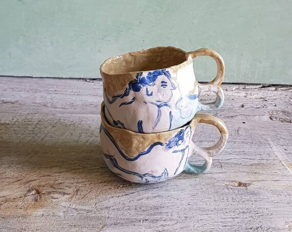 A pottery mug with a nude drawing, it has a double handles. A drawing of blue woman, sky blue and a large opening for breakfast.