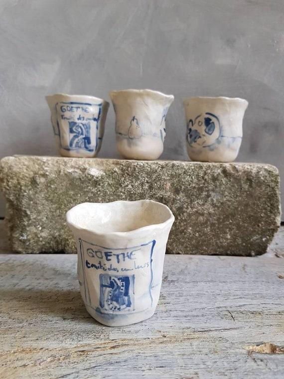 Tasse à café expresso artisanale bleuet blanc. Tasse en poterie avec dessin de poire, livre et palette de peinture.