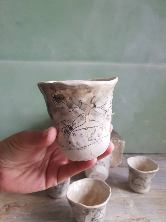 Black and white artisan coffee cup. Pottery cup with flower drawing.