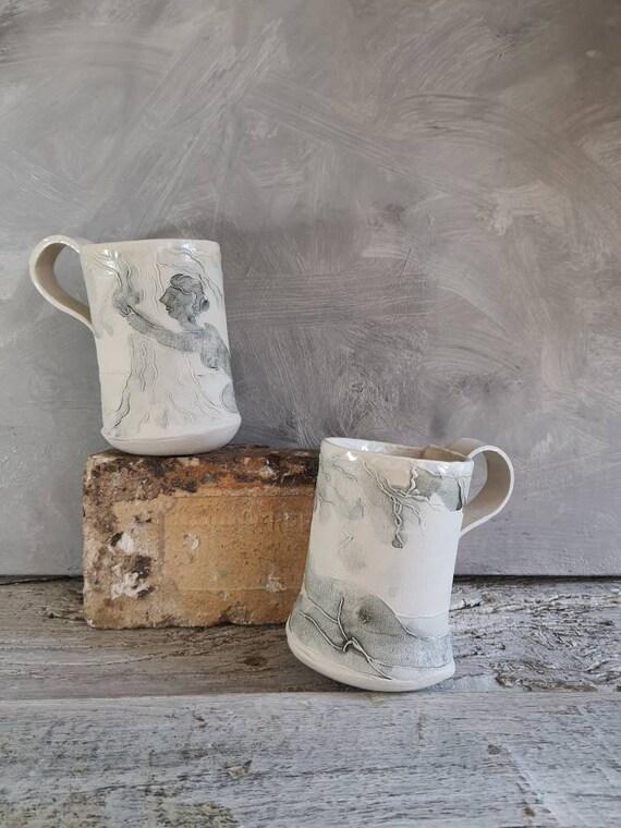Mug en poterie artisanale . Tasse en céramique gris et blanc dessin de femme avec un arbre. Vente en ligne de mug artisanal.