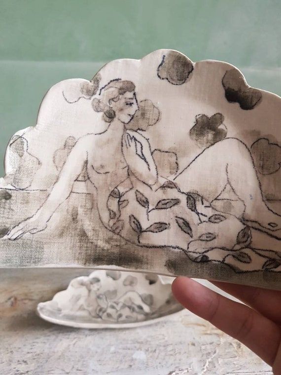 Cloud-shaped plate with woman drawing. Small plate of handcrafted pottery decoré of a drawing of a.