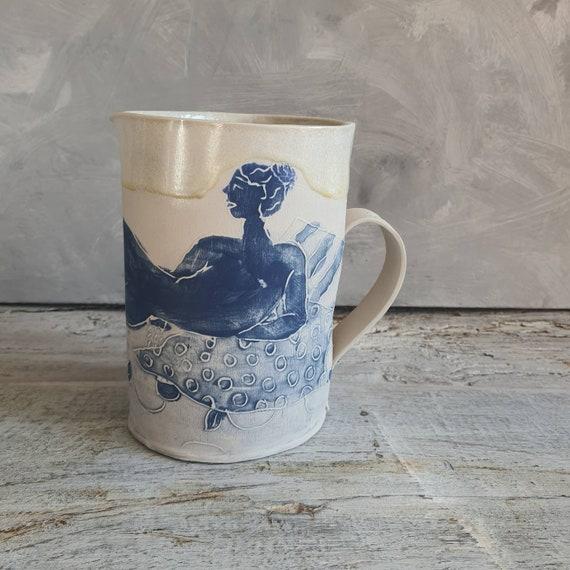 Pichet en poterie artisanale avec poignée décoré avec un dessin de femme nu et d'un émail crème, cruche en grès artisanale.