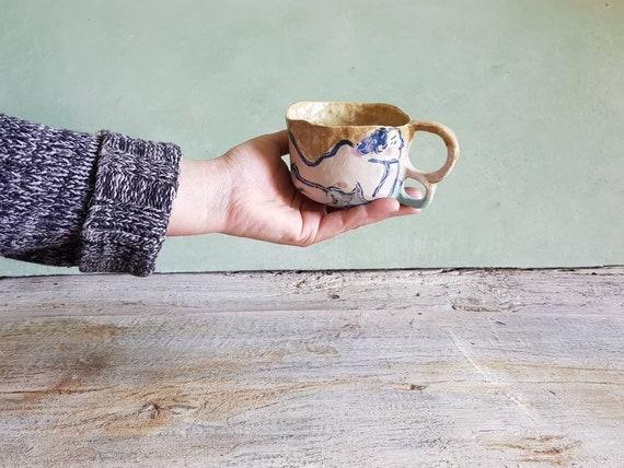 Mug en poterie avec dessin de nue, il a une double anse. Une dessin de femme bleu, bleu ciel et une grande ouverture pour le petit déjeuner.