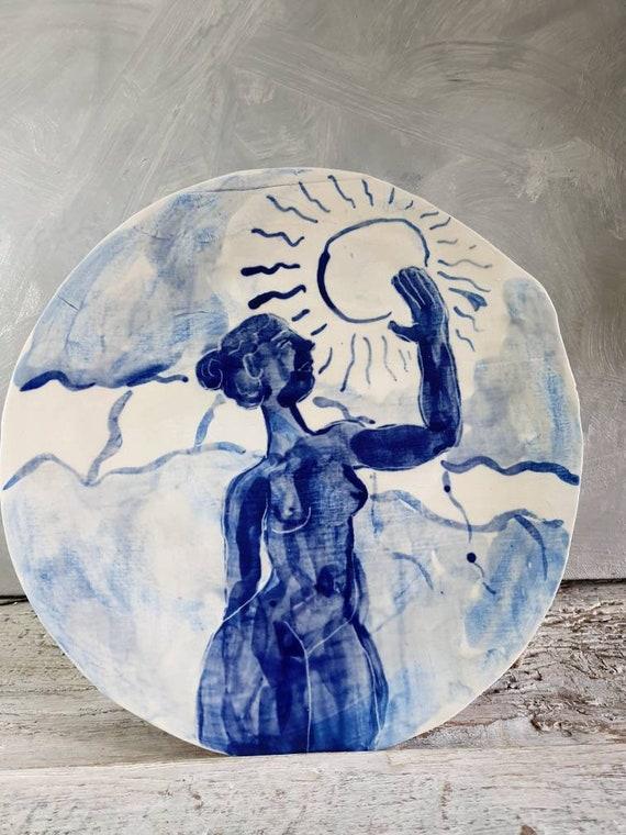 Assiette avec dessin femme avex le soleil, c'est une grande assiette en grès un dessin de lune bleu et blanc. Piece-unique.