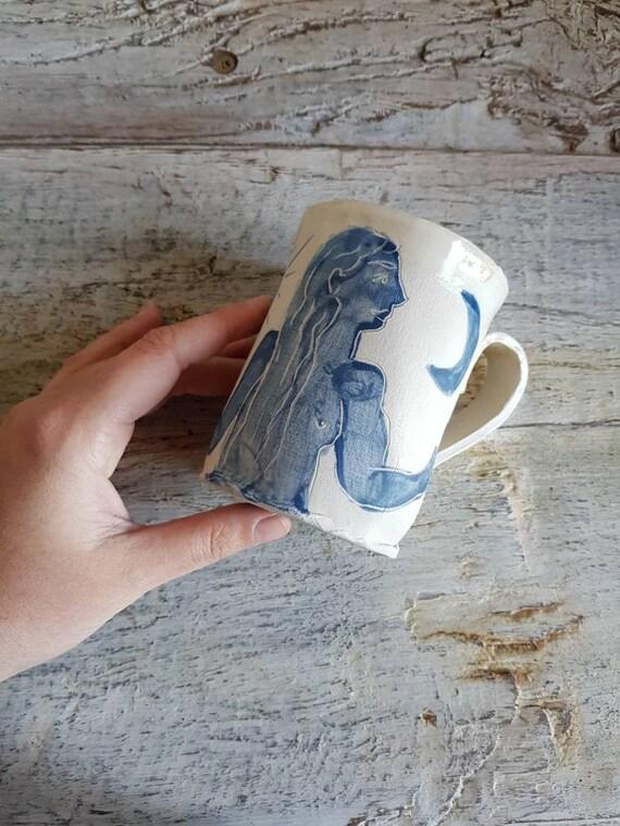 Mug en poterie artisanale . Décorée avec un dessin de village et un émail vert céladon  et bleuté  . Vente en ligne de mug artisanal.