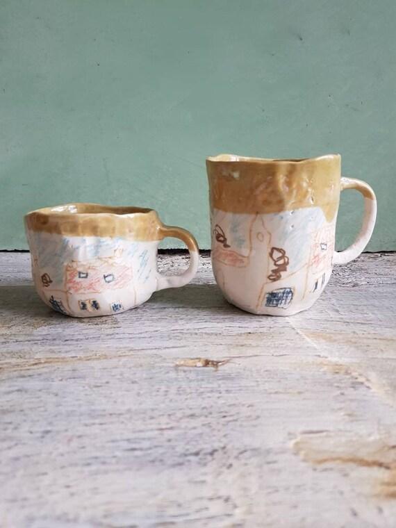 Tasse en poterie artisanale avec anse et dessin. Grand mug en grès avec dessin de village en couleur.