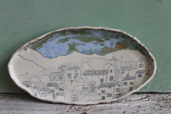 Large oval plate in white stoneware with village design.