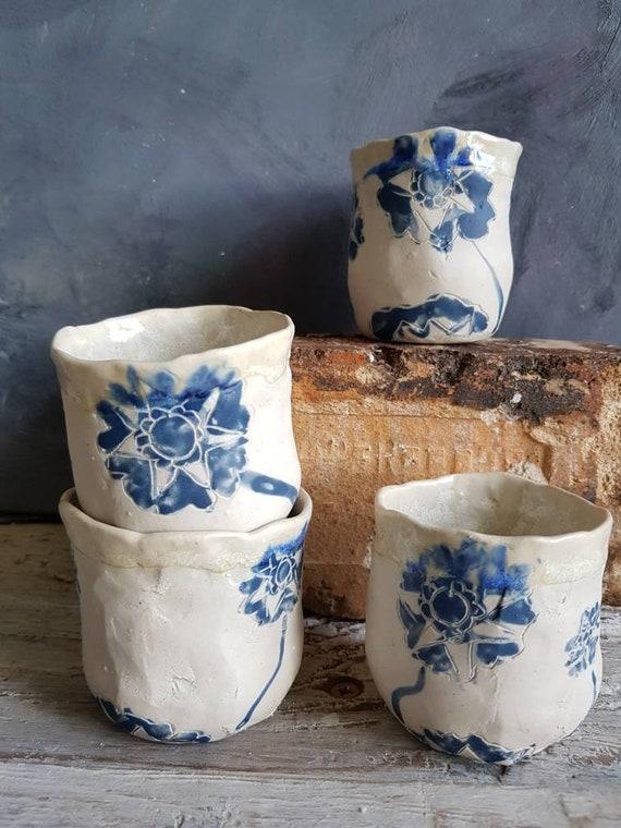 Tasse à café expresso artisanale bleue et blanche. Tasse en poterie avec dessin de fleurs tournesol.